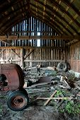 Old Wooden Barn Full Of Junk And Rusting Tractor
