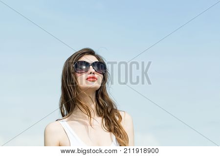 poster of Girl in white swimsuit and glasses. Fashion model on blue sky background. Beauty and summer fashion. vacation and relax. Woman with long brunette hair and red lips copy space