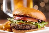 stock photo of fried onion  - gourmet cheeseburger with mug of beer in background - JPG