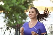Overweight young woman jogging in park. Weight loss concept poster
