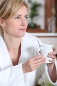 Pensive woman having a morning cup of coffee in her bathrobe