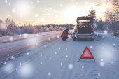 Broken car on a snowy winter road poster