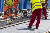 Workers Construct Asphalt Road And Railroad Lines poster