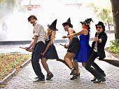 Grupo de pessoas na fantasia de bruxa de vassoura e halloween no exterior.