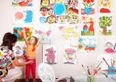 Child with teacher draw paints in playroom. Preschool.