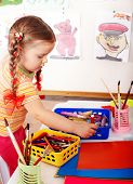 Child  prescooler with colour pencil in play room.