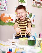 Boy with brush draw red sun in play room. Preschool.