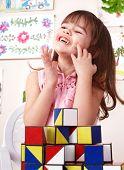 Child playing  block in play room. Preschool.