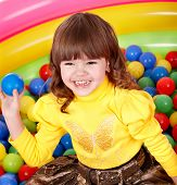 Little girl  in group colourful ball.