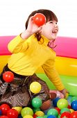 Happy little girl in group colourful ball. Isolated.