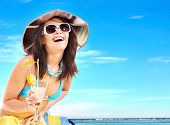 stock photo of beach holiday  - Girl in bikini drink juice through a straw - JPG