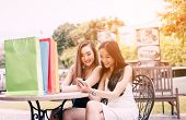 Two Asian Woman Sitting At Store Cafe With Happy Watching Smartphone At Shopping Mall Center. poster