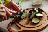 Hand Cutting Vegetables In Kitchen. Woman Cuts Eggplant On A Cutting Board. poster