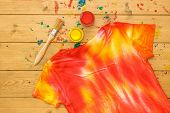 T-shirt Decorated In Tie Dye Style In Yellow And Red Colors On A Wooden Table. Staining Fabric In Ti poster