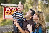 foto of real  - Happy Mixed Race Couple with Baby in Front of Sold Real Estate Sign - JPG