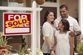 Hispanic Mother, Father and Daughter in Front of Their New Home with Sold Home For Sale Real Estate