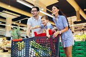 Happy Family With Child And Shopping Cart Buying Food At Grocery Store Or Supermarket poster
