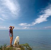 Girl And Dog Standing On Precipice And Looking To The Sea