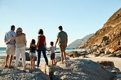 Three generation white family on a beach stand holding hands, admiring view, full length, back view poster