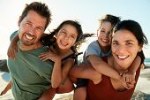 Mid adult white parents piggybacking their kids on a beach, smiling to camera, close up, backlit poster