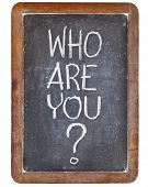 who are you question - white chalk handwriting on vintage slate blackboard, isolated on white