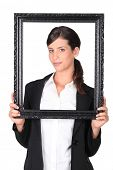 Woman holding empty picture frame