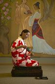 Woman in kimono pouring tea in spa room