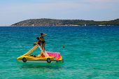 Slender Girls In Bathing Suits Float On An Inflatable Boat On The Beautiful Sea In Sibenik, Croatia, poster
