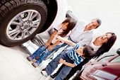 Family buying a car and pointing at the wheels