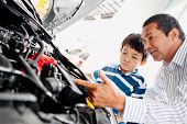 Father buying car with his son and explaining to him about mechanics
