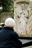 picture of polonia  - elderly woman visiting grave on Old Powazki Cemetery in Warsaw Poland - JPG