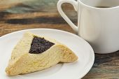 fruit hamantaschen cookie  on a plate with a cup of coffee - a traditional pastry in Ashkenazi Jewis