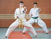 stock photo of taekwondo  - Two young adult people in kimono training taekwondo martial art at gym - JPG