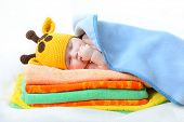 cute sleeping baby boy in funny hand made giraffe hat, beautiful kid dozing on pile of colorful towe