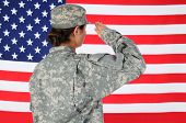 Closeup of an American Female Soldier in combat uniform saluting a flag. Seen from behind horizontal