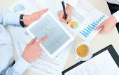 stock photo of graph paper  - Business team analyzing income charts and graphs with modern apple ipad - JPG