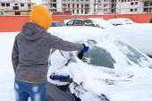picture of ice-scraper  - Woman scraping ice from the car window in winter time - JPG
