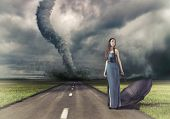woman,with umbrella on the road and tornado