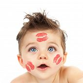 Picture of small cute Cupid, closeup portrait of pretty child with red kisses on his cheeks isolated