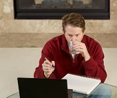 Mature Man Drinking Water While Working On Assignments At Home