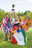 Portrait of successful athletes with various national flags celebrating in park