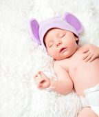 stock photo of fancy mouse  - cute newborn baby sleeps in a mouse hat with ears - JPG