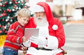 Boy and Santa Claus using digital tablet together in courtyard