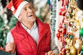 Happy senior man selecting Christmas ornaments at store