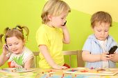 foto of toy phone  - Three children with the phones in hand at the table with toys - JPG