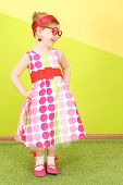 Mod little girl in a bright dress and large red glasses, hands on belt