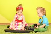 Mods boy and girl in bright clothes sitting on the floor in front of a toy piano
