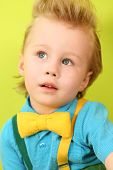 Portrait of mod little boy in blue checkered shirt and a yellow bow tie