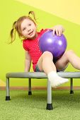 Funny little girl with pigtails sitting on a trampoline with a purple ball