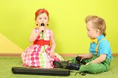 Boy and girl sitting on the floor in front of a toy piano, a girl singing into a microphone